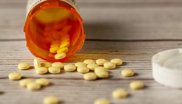 prescription bottle of small yellow pills knocked over on its side with pills spilling out - Klonopin addiction