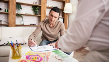 man doing art therapy in therapist's office - residential addiction treatment